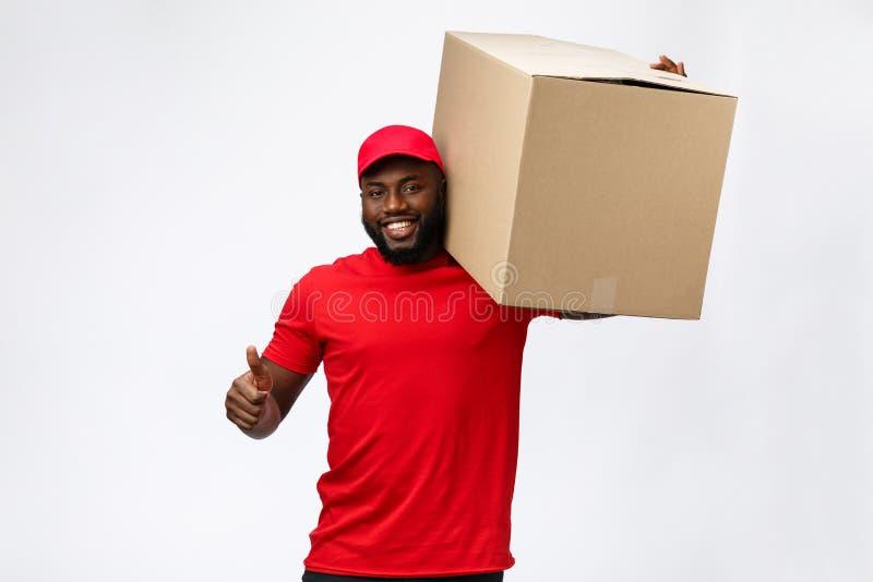 Conceito da entrega - caixa levando afro-americano considerável do pacote do homem de entrega Isolado no fundo cinzento do estúdi fotografia de stock royalty free