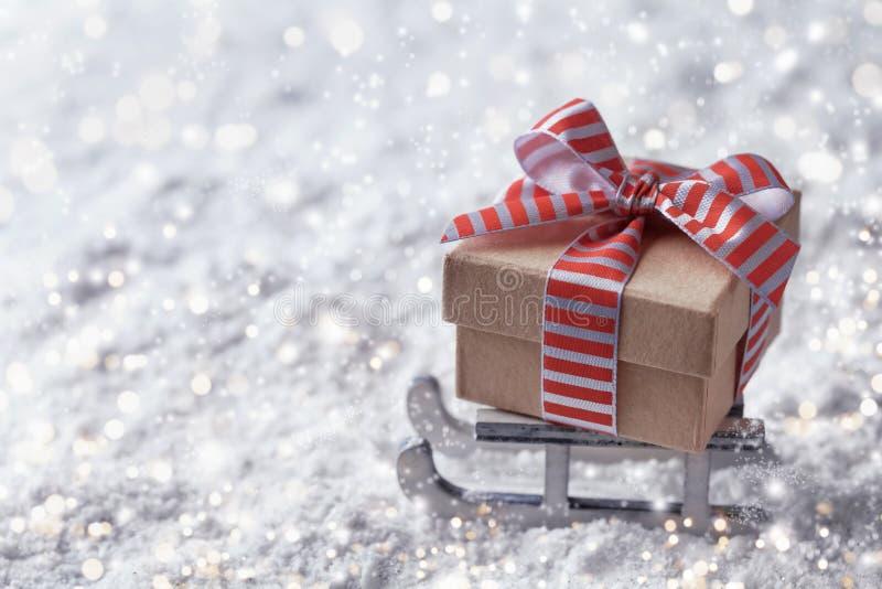 Conceito da entrega do Natal ou do ano novo Trenó com uma caixa de presente na neve fotografia de stock royalty free