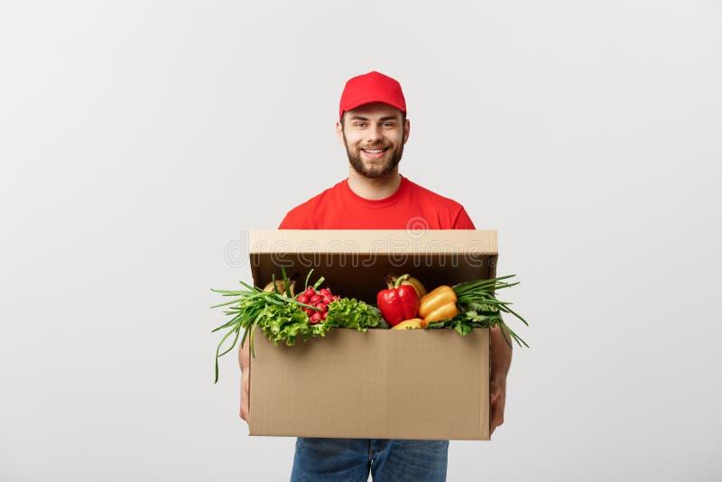 Conceito da entrega: Homem caucasiano considerável do correio da entrega do mantimento no uniforme vermelho com a caixa do mantim fotos de stock