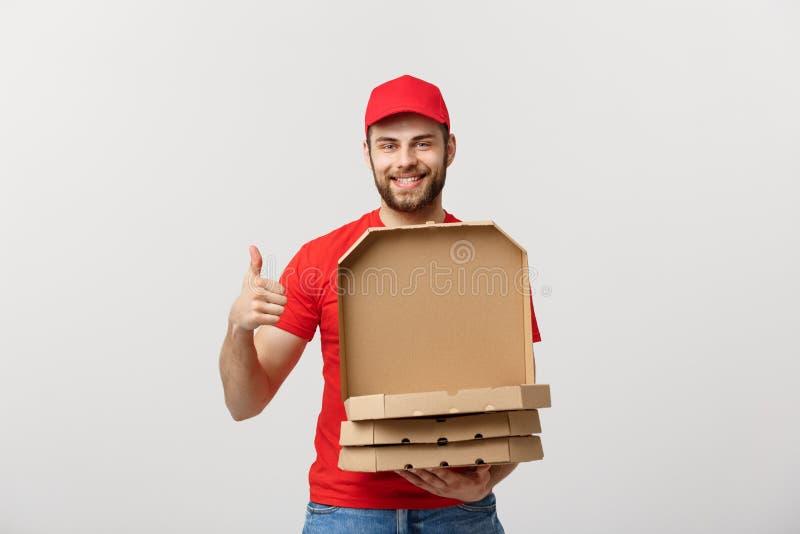 Conceito da entrega da pizza O menino novo é de fornecimento e mostrando caixas da pizza em umas caixas Isolado no fundo branco foto de stock