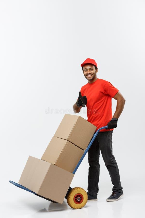Conceito da entrega - retrato do homem ou do correio afro-americano considerável de entrega que empurram o caminhão de mão com a  imagens de stock royalty free
