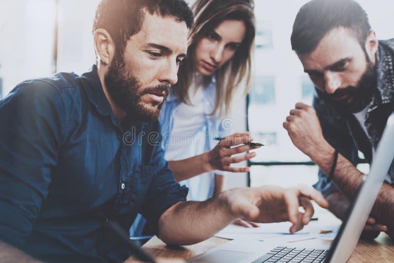 Conceito da equipe do negócio Os profissionais novos que discutem o negócio novo projetam-se no escritório moderno O grupo de trê imagens de stock