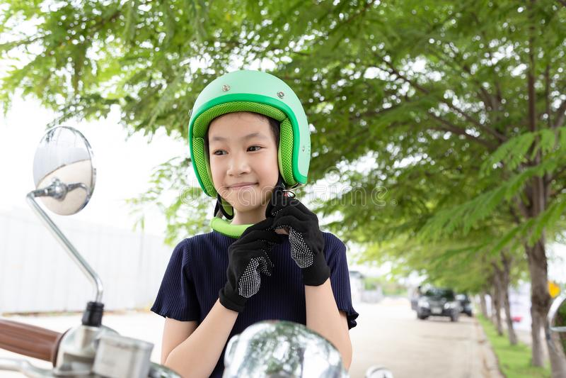 Conceito da equita??o da seguran?a Menina asiática feliz antes de montar no velomotor com capacete, motociclista que veste o capa fotos de stock royalty free