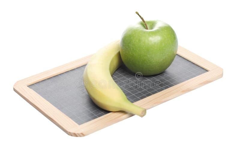 Conceito da escola: uma maçã verde e uma banana em uma placa de giz isolada no fundo branco imagens de stock royalty free