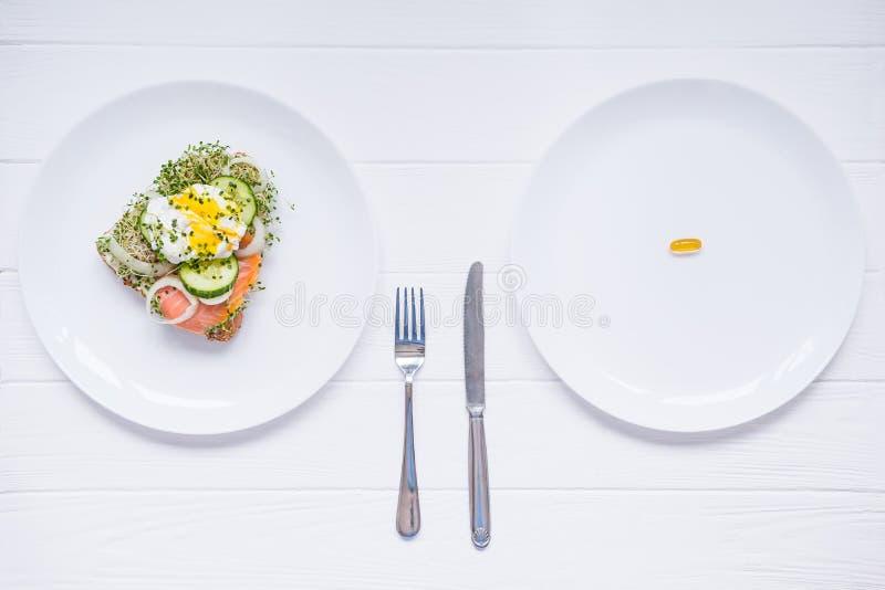 Conceito da escolha - alimento saudável ou comprimidos médicos, vista superior na placa branca e tabela de madeira Escolha entre  fotos de stock