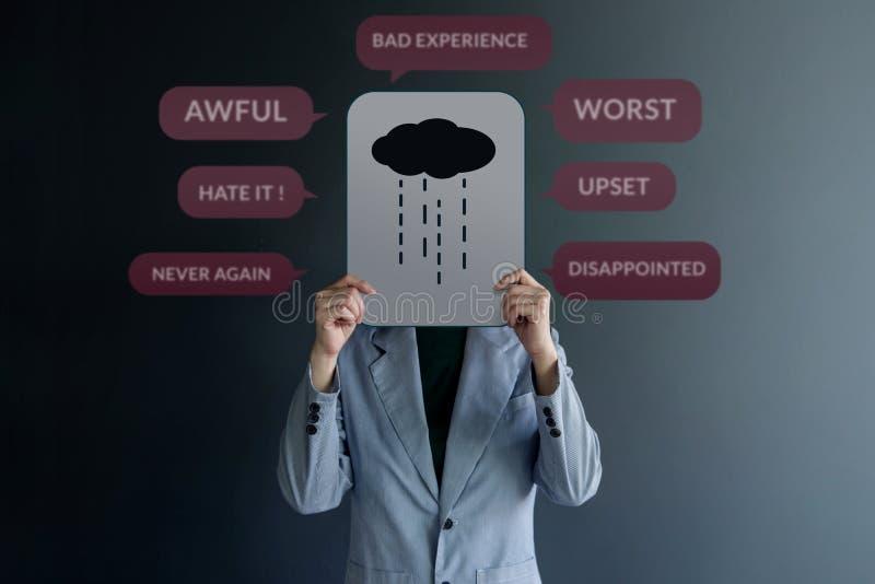 Conceito da experiência do cliente Posição do cliente de Uhappy na parede com sinal da tristeza no papel Cercado pela revisão neg fotos de stock