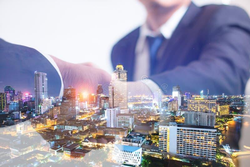 Conceito da exposição dobro Aperto de mão do negócio do acionista com fundo da noite da cidade Homem de negócios que agita as mão imagem de stock royalty free