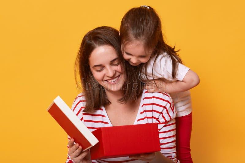 Conceito da família, da criança, do feriado e do dia de mãe Jovem mulher de sorriso em camisa listrada que senta-se com sua filha foto de stock