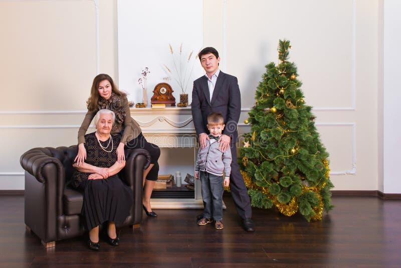Conceito da família, dos feriados, da geração, do Natal e dos povos - família de sorriso perto da árvore do xmas imagens de stock