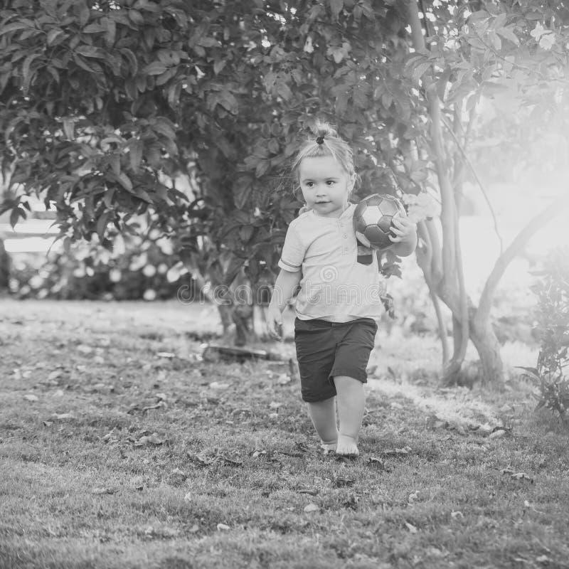 Conceito da felicidade das crianças da infância da criança Brincadeira com a bola na grama verde no dia idílico foto de stock