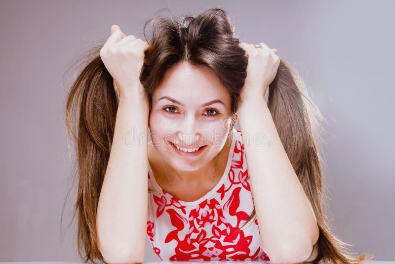 Conceito da felicidade e da beleza Retrato da mulher de sorriso bonita nova que joga com seu cabelo longo fotografia de stock