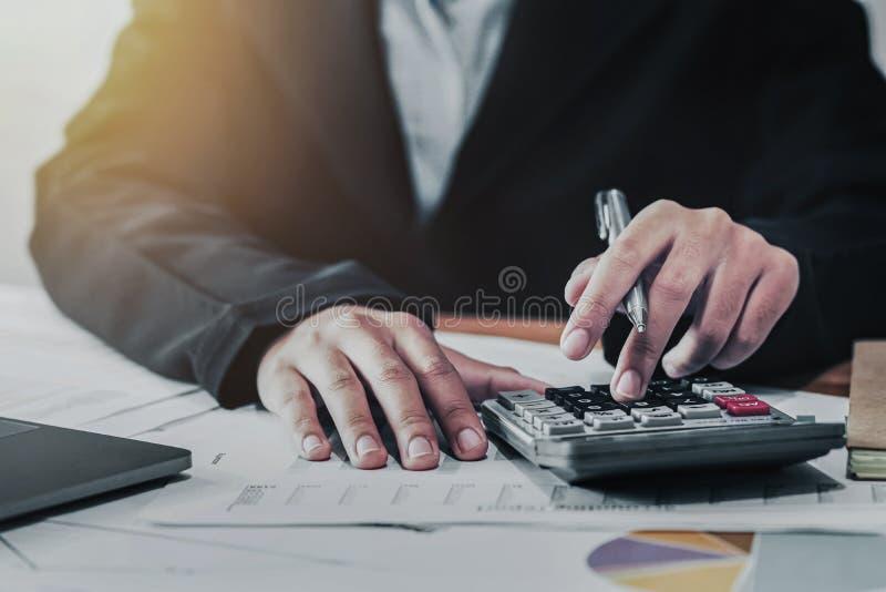 conceito da finança da contabilidade da empresa o contador que usa a calculadora para calcula com funcionamento do portátil no es foto de stock royalty free