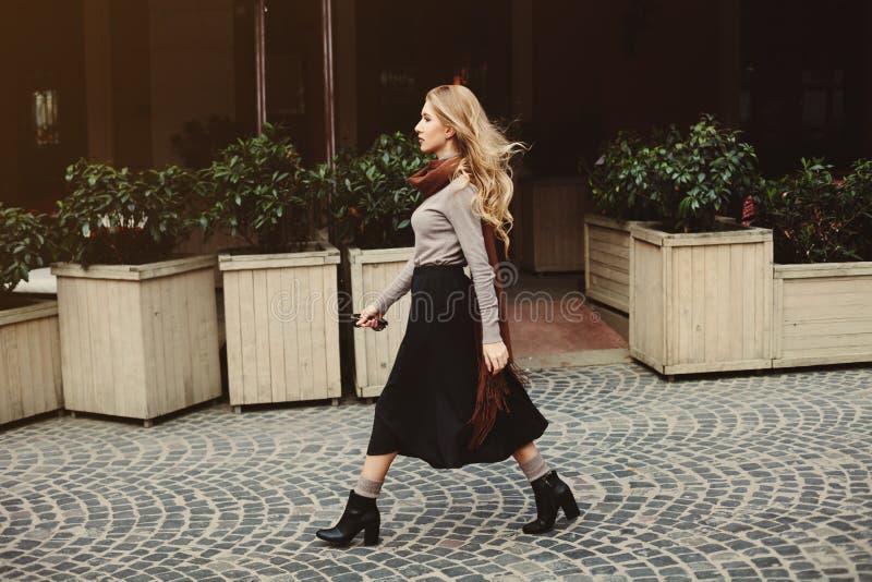 Conceito da forma da rua: retrato completo do corpo da mulher bonita nova que anda na cidade Foto tonificada e filtrada imagem de stock