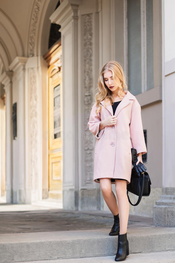 Conceito da forma da rua: retrato da mulher bonita nova que veste o revestimento cor-de-rosa com a bolsa que anda na cidade velho fotografia de stock royalty free