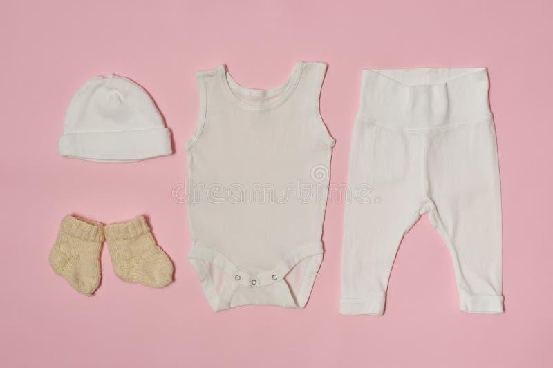 Conceito da forma do bebê em um fundo cor-de-rosa Tampão, bodysuit, calças e peúgas imagens de stock royalty free
