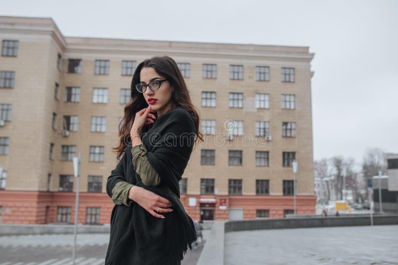 Conceito da forma: moça bonita com cabelo longo, vidros, os bordos vermelhos que estão perto da parede moderna que veste no terno fotografia de stock royalty free