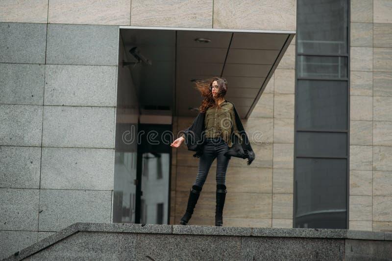 Conceito da forma: moça bonita com cabelo longo, vidros, os bordos vermelhos que estão perto da parede moderna que veste no terno imagem de stock