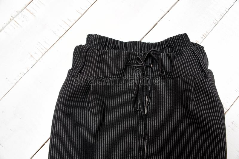 Conceito da forma da roupa Detalhe de calças preta no fundo de madeira branco Vista superior imagens de stock