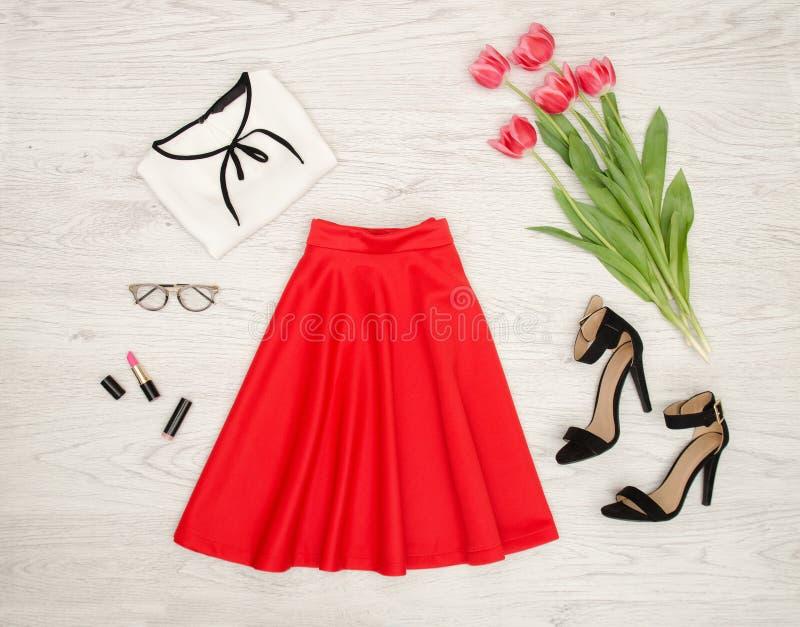 Conceito da forma Saia vermelha, blusa, óculos de sol, batom, sapatas pretas e tulipas cor-de-rosa Vista superior, fundo de madei foto de stock