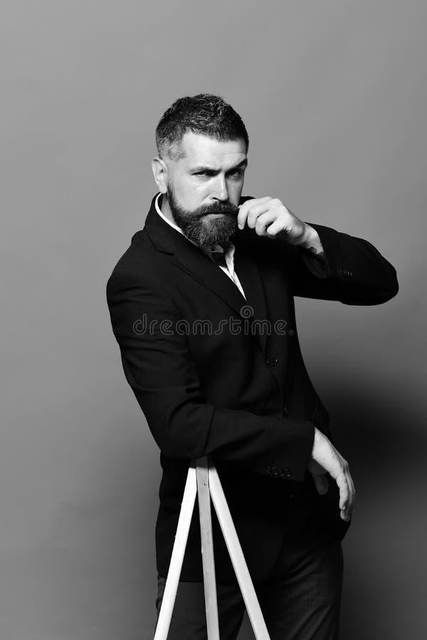 Conceito da fotografia e da profissão O homem macho inclina-se no tripé da foto fotos de stock