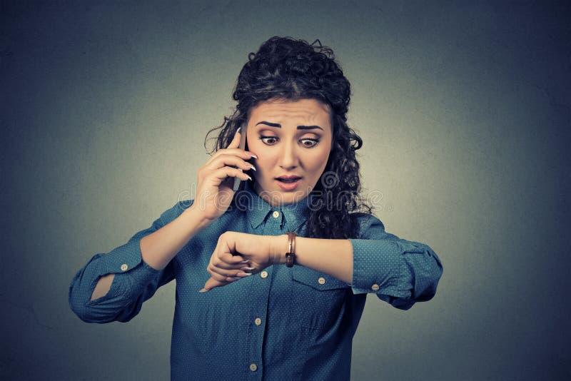 Conceito da gestão de tempo Mulher de negócios forçada que olha o relógio de pulso, correndo tarde foto de stock