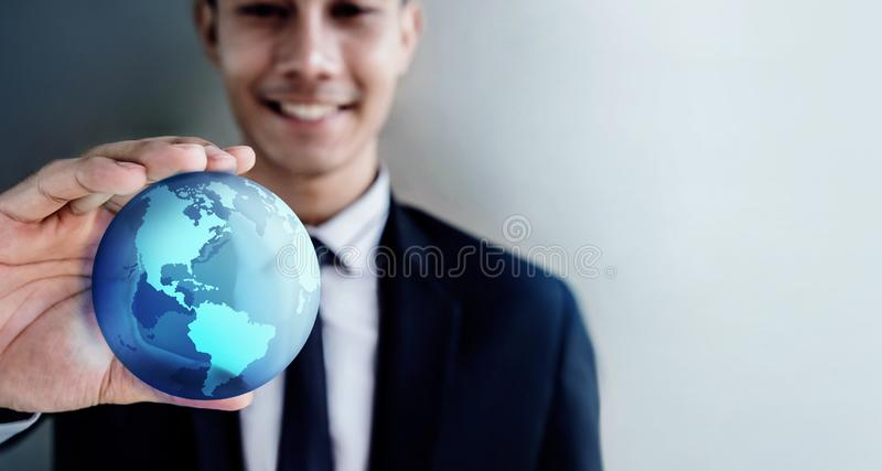 Conceito da globaliza??o Homem de negócios profissional de sorriso feliz que guarda um globo azul transparente do mundo imagem de stock royalty free