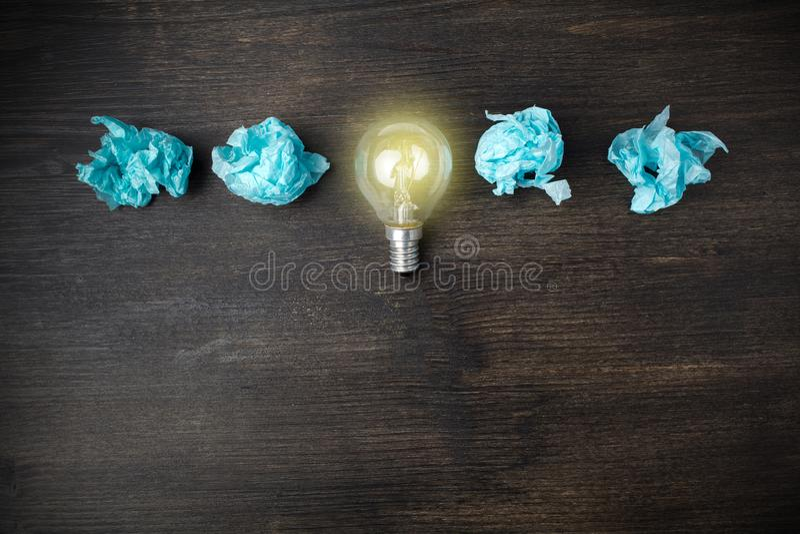 Conceito da grande ideia com luz amarrotada - papel azul e ampola no fundo de madeira fotografia de stock royalty free