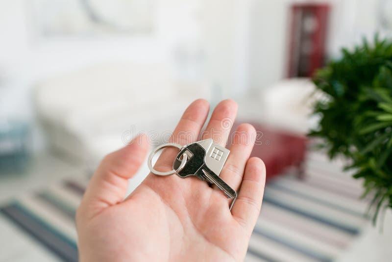 Conceito da hipoteca Os homens entregam guardar chave com keychain da casa Interior claro moderno da entrada Bens imobiliários, c imagens de stock