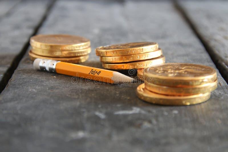 Conceito da ideia do negócio Inscrição em moedas do lápis e de ouro imagens de stock royalty free