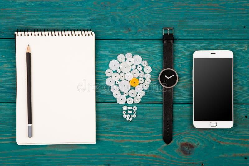 conceito da ideia - sinal, bloco de notas, relógio e telefone do bulbo na mesa foto de stock royalty free