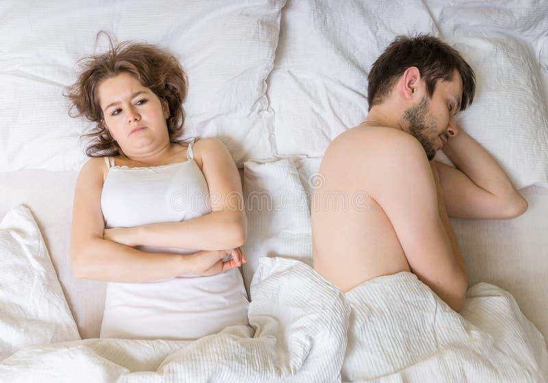 Conceito da impotência O homem novo está dormindo na cama Amiga triste, desapontado e insatisfeita fotografia de stock