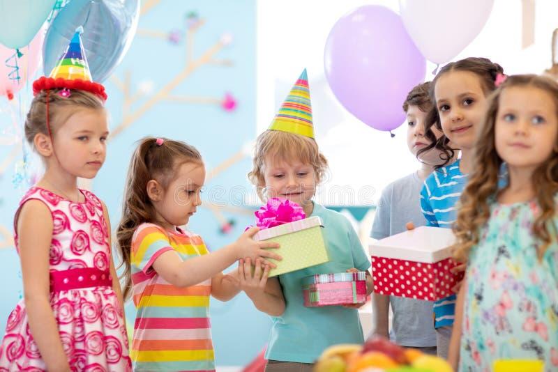 Conceito da infância, dos feriados, da celebração e da amizade Crianças felizes nos chapéus do partido que dão presentes na festa imagens de stock