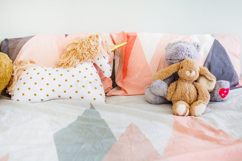 Conceito da infância Os brinquedos puseram sobre o roupa de cama no close-up da sala de sono imagem de stock royalty free