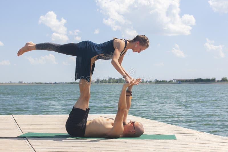 Conceito da ioga de Acro Pares da ioga Pares de lição praticando da ioga dos povos desportivos novos com sócio, homem e mulher no fotografia de stock