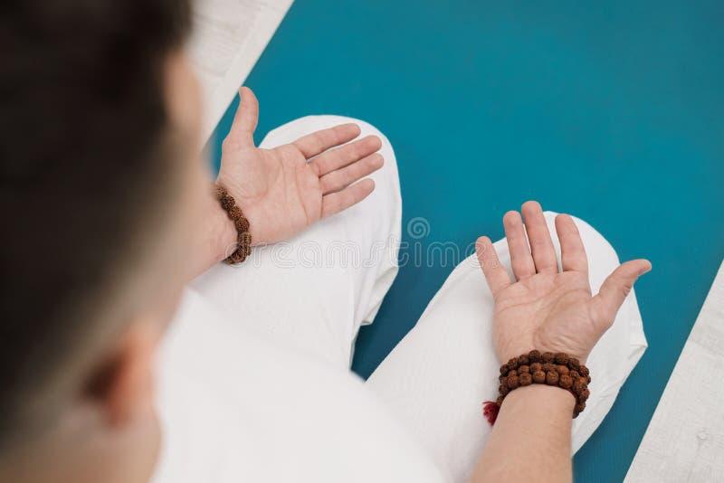 Conceito da ioga e da meditação Close-up, mãos de um homem na roupa branca, dobradas na oração Fundo e amarelo brancos fotos de stock royalty free