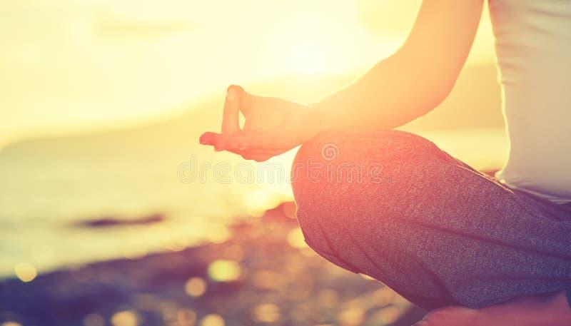 Conceito da ioga pose praticando dos lótus da mulher da mão na praia fotos de stock royalty free