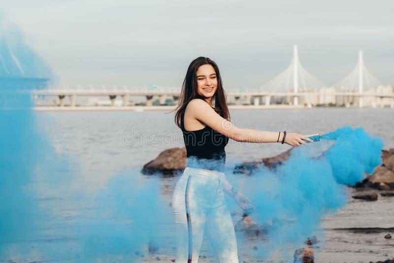Conceito da juventude e da alegria A moça feliz bonita no beira-mar guarda bombas de fumo acima colorido da luz teens imagem de stock