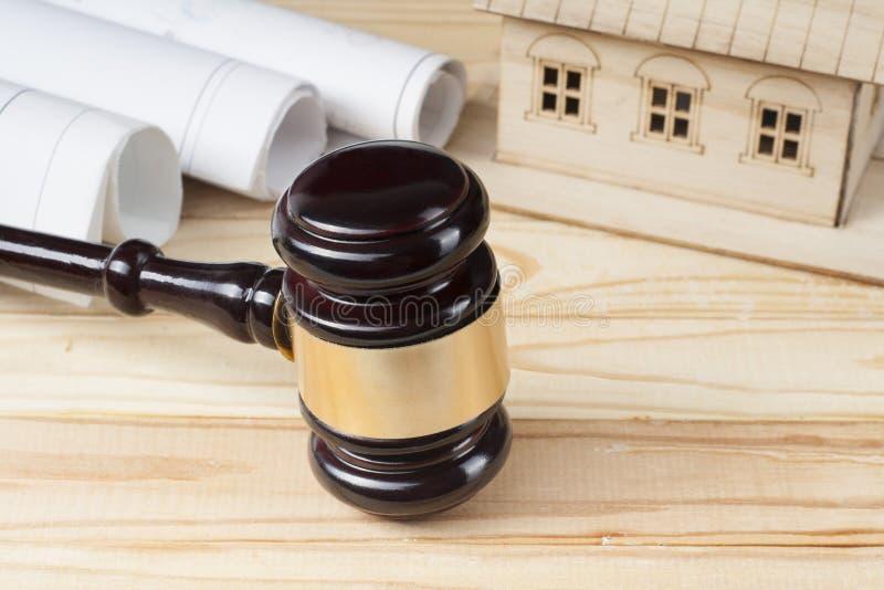 Conceito da lei e da construção Casa modelo, desenhos e martelo de madeira do juiz na tabela imagens de stock