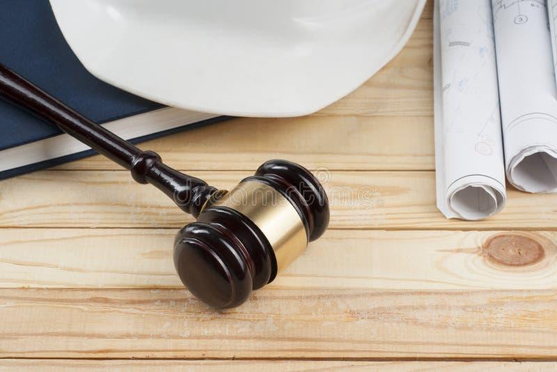 Conceito da lei e da construção Martelo de madeira do juiz, desenhos e capacete branco na tabela fotografia de stock