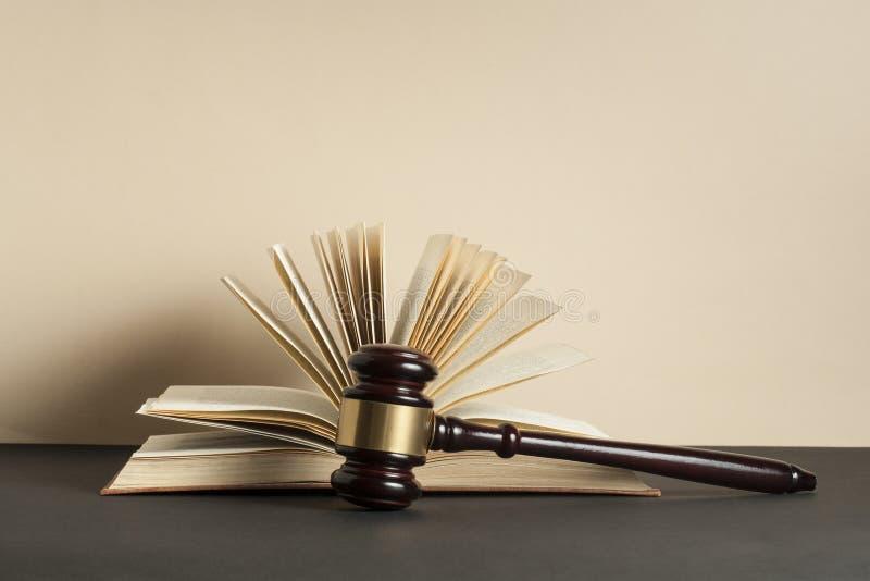 Conceito da LEI Livro aberto com o martelo de madeira do juiz na tabela em uma sala do tribunal imagem de stock