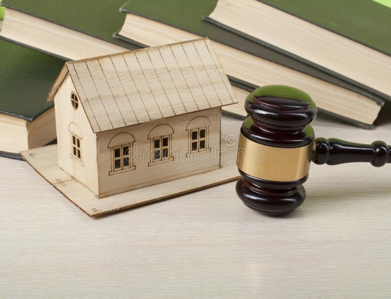 Conceito da lei - livros, casa modelo com o martelo de madeira do juiz na tabela Copie o espaço para o texto foto de stock