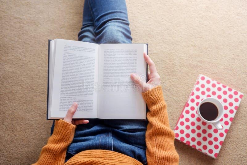 Conceito da leitura Foco macio da jovem mulher que relaxa pelo livro e imagem de stock royalty free