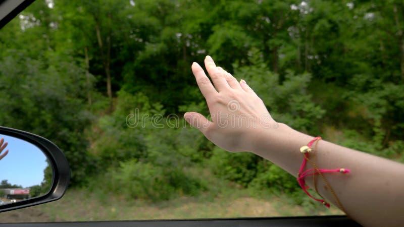 Conceito da liberdade, do autotravel e da aventura Um motorista da mulher sente o vento através de suas mãos ao conduzir ao longo fotos de stock royalty free