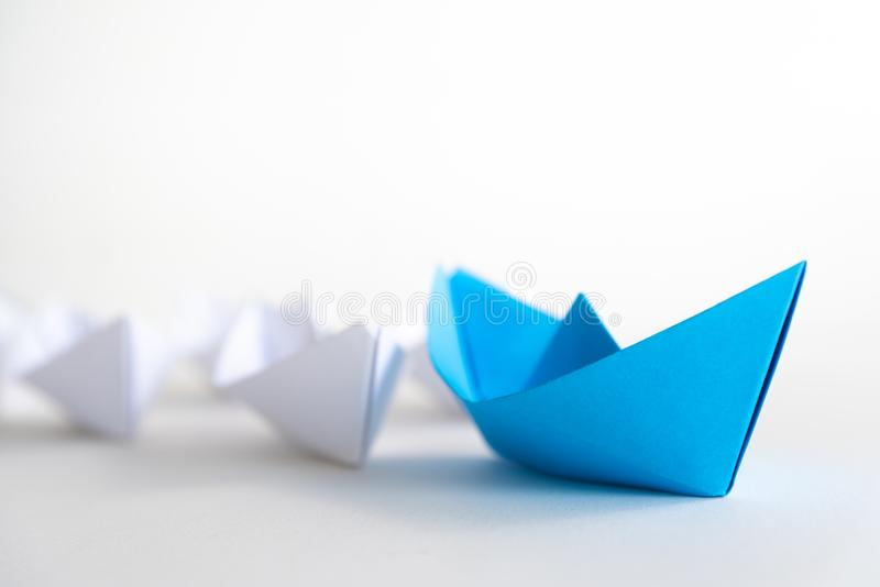 Conceito da liderança ligação do navio do papel azul entre o branco imagens de stock