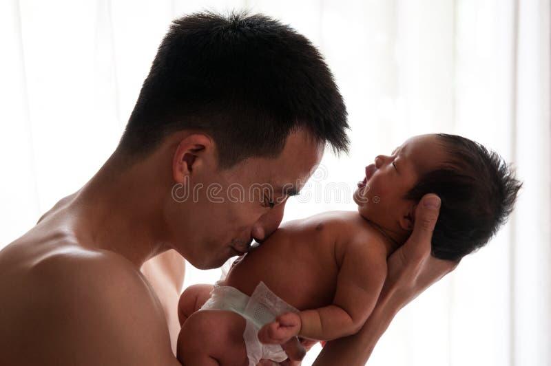 Conceito da ligação do dia do pai com cuidados recém-nascidos do bebê O pai é de jogo e de fala com o bebê recém-nascido ao lado  imagens de stock