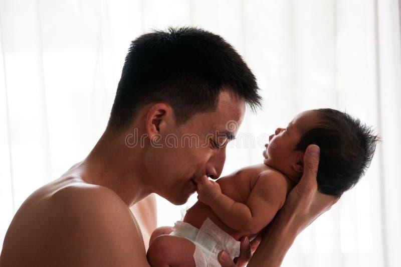 Conceito da ligação do dia do pai com cuidados recém-nascidos do bebê O pai é de jogo e de fala com o bebê recém-nascido ao lado  imagens de stock royalty free