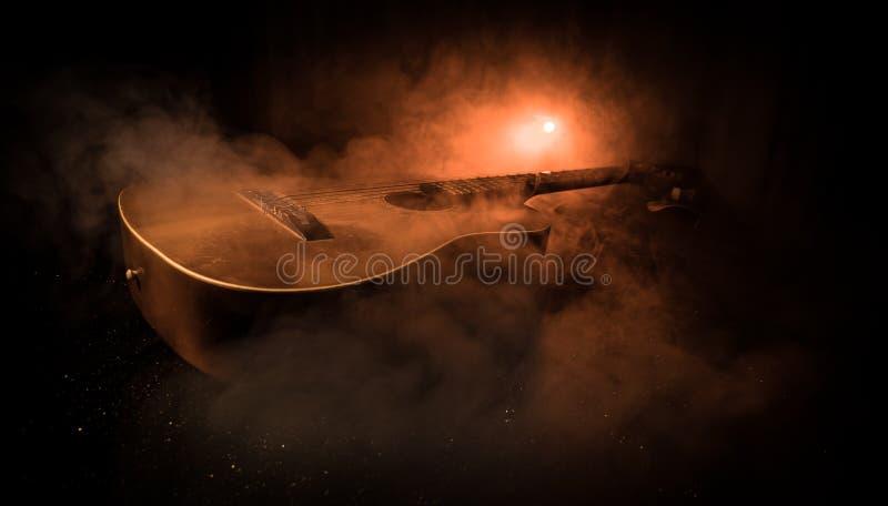 Conceito da música Guitarra acústica em um fundo escuro sob o feixe de luz com fumo Guitarra com cordas, fim acima Foco seletivo fotos de stock royalty free