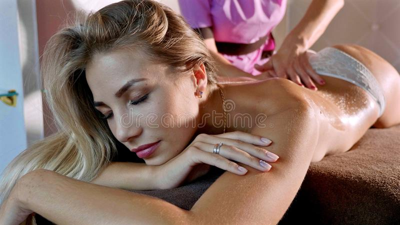 Conceito da massagem Massagem relxing reciving da jovem mulher bonita no salão de beleza dos termas fotografia de stock