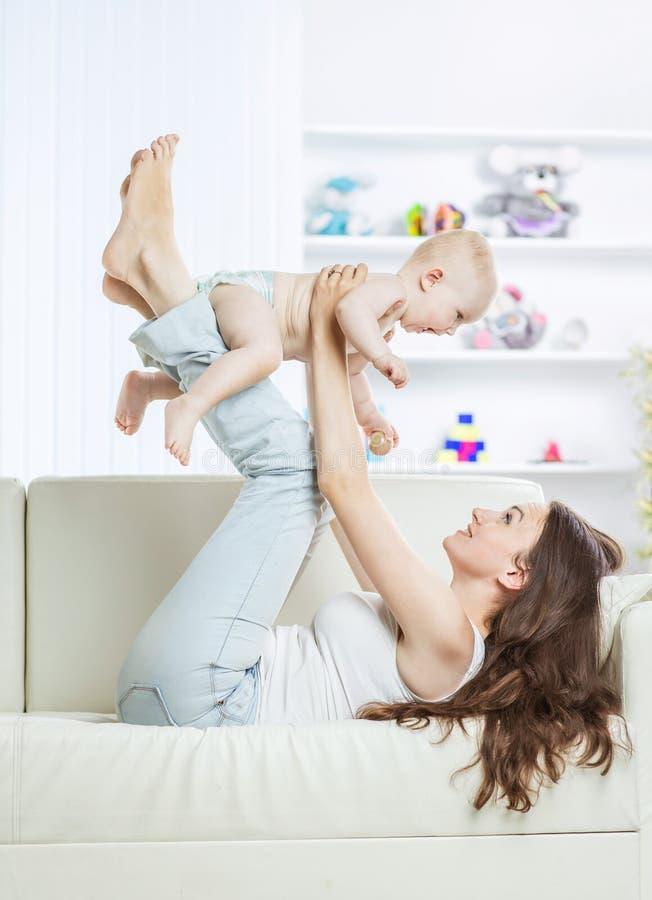 Conceito da maternidade: mãe feliz que joga com o bebê do bebê de um ano na sala para crianças fotos de stock royalty free
