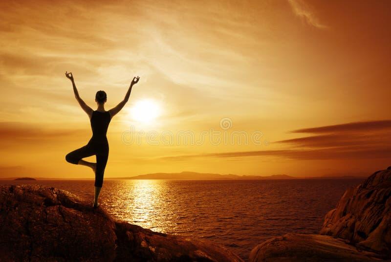 Conceito da meditação da ioga, silhueta da mulher que medita na natureza imagens de stock